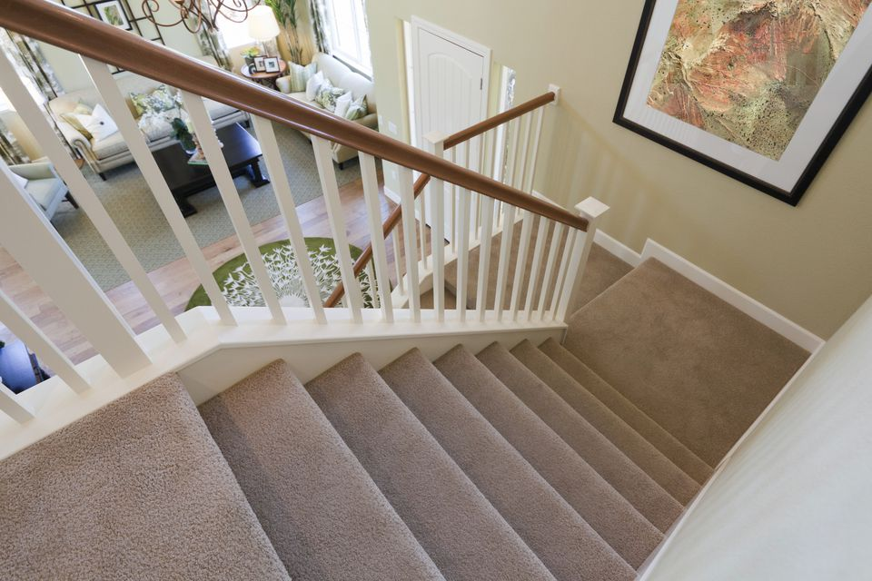 Staircase in a home featuring a beige carpet
