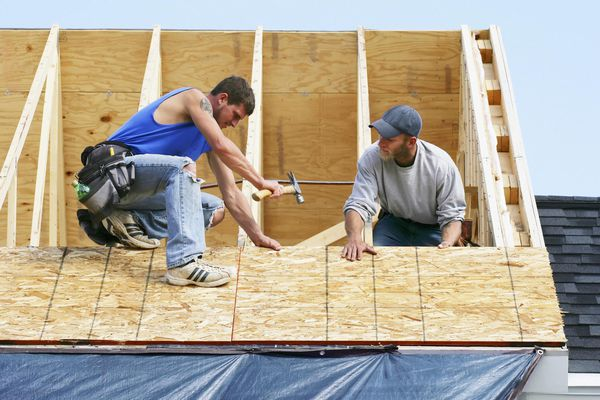 Construction workers on a roof of home