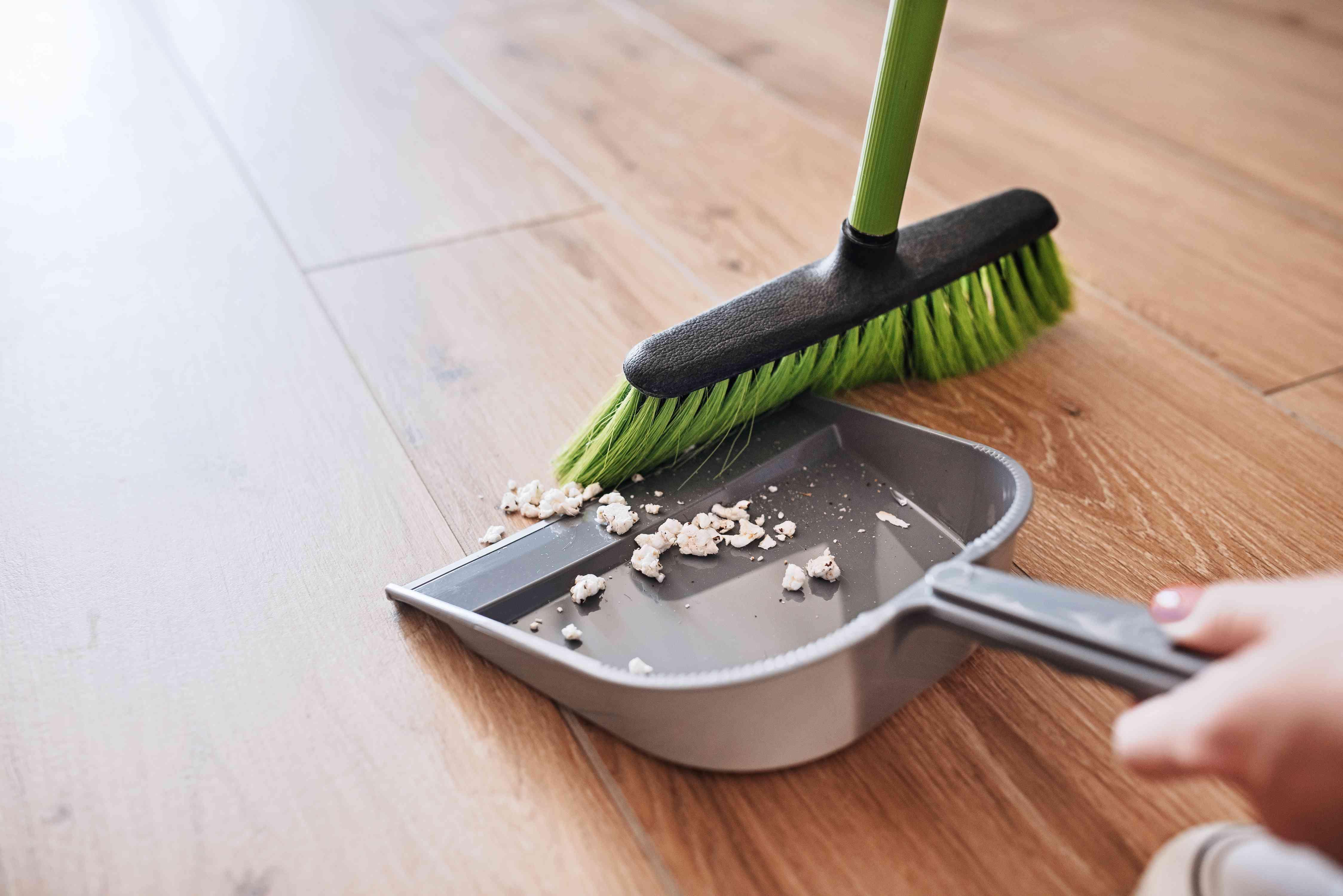 Green broom sweeping up white debris in gray dustpan