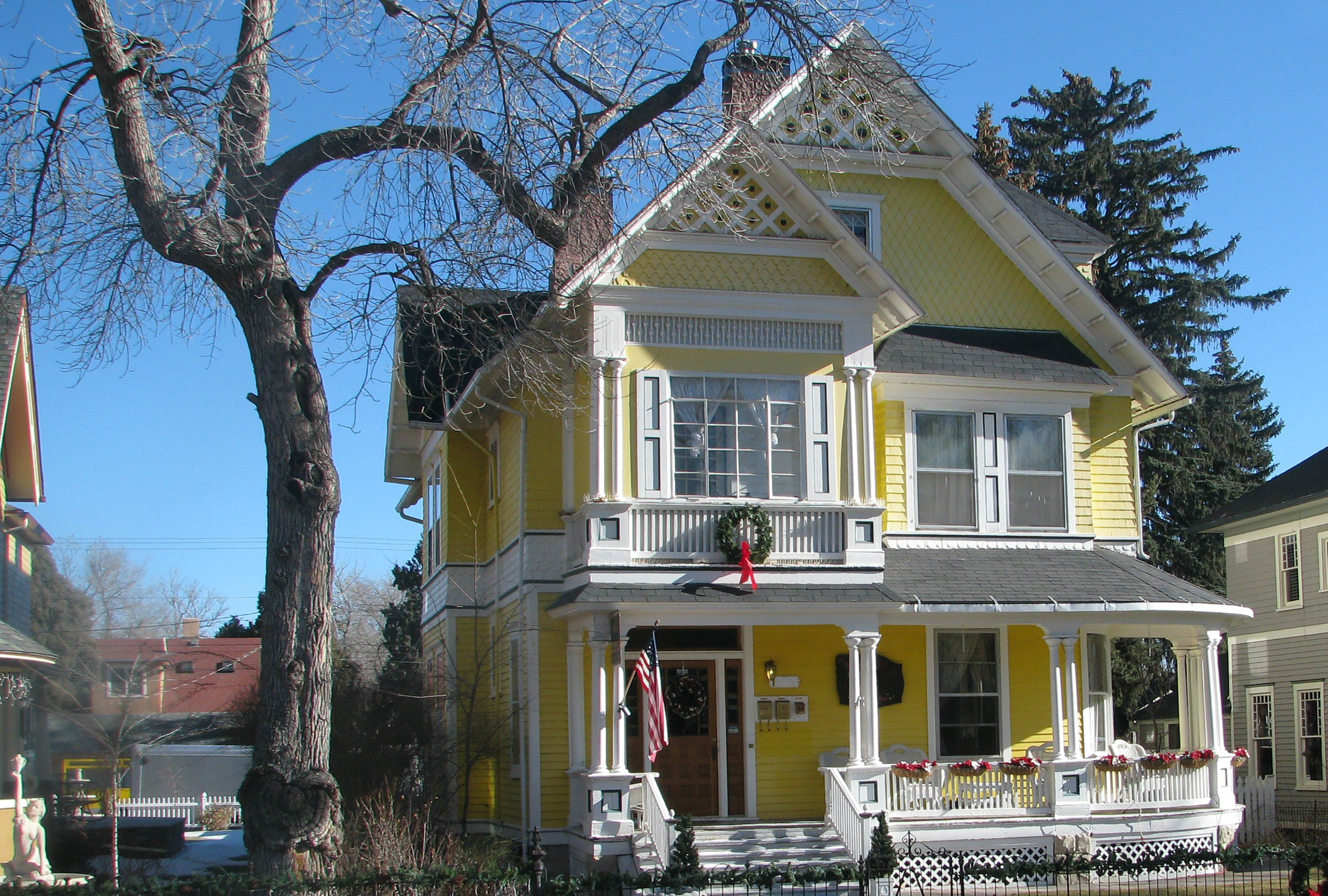 yellow house with white trim, two-story, front gable with attic window on third story, white lattice in peaks of gables, front porch on first floor and enclosed porch on second story, gable on side