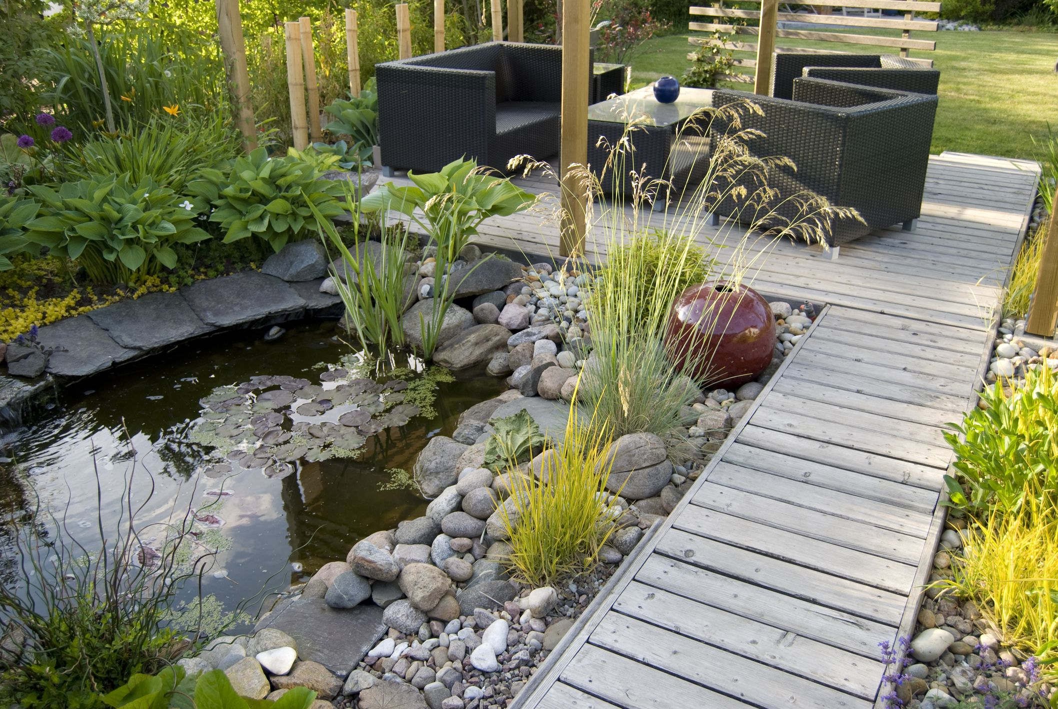 Garden pond surrounded by rock, off a walkway and patio.
