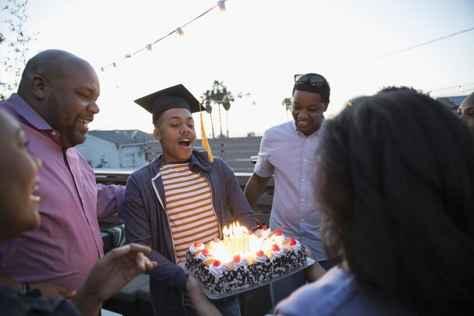 African American family celebrating graduation with cake on deck