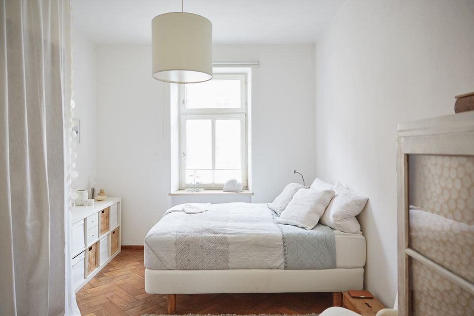 White coloured bedroom with parquet floor, bed and cupboards