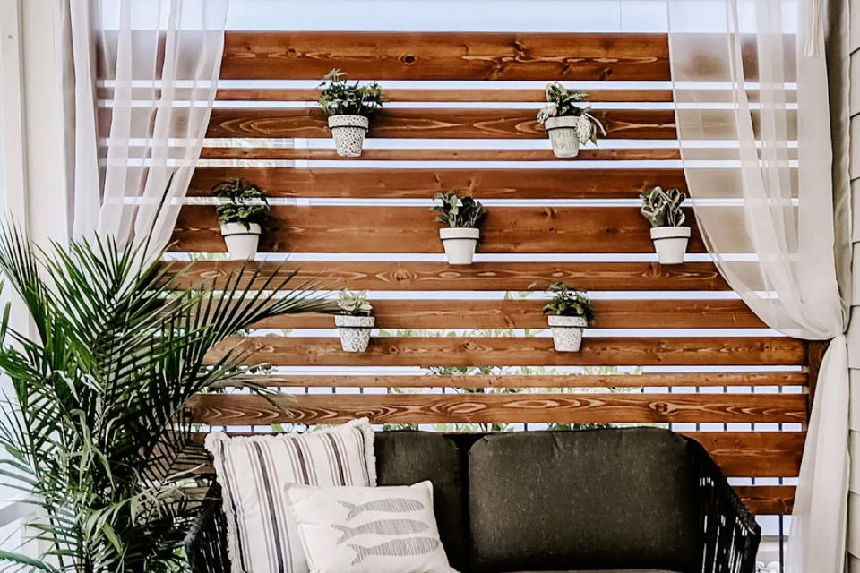 A wooden privacy screen with plants hanging on it