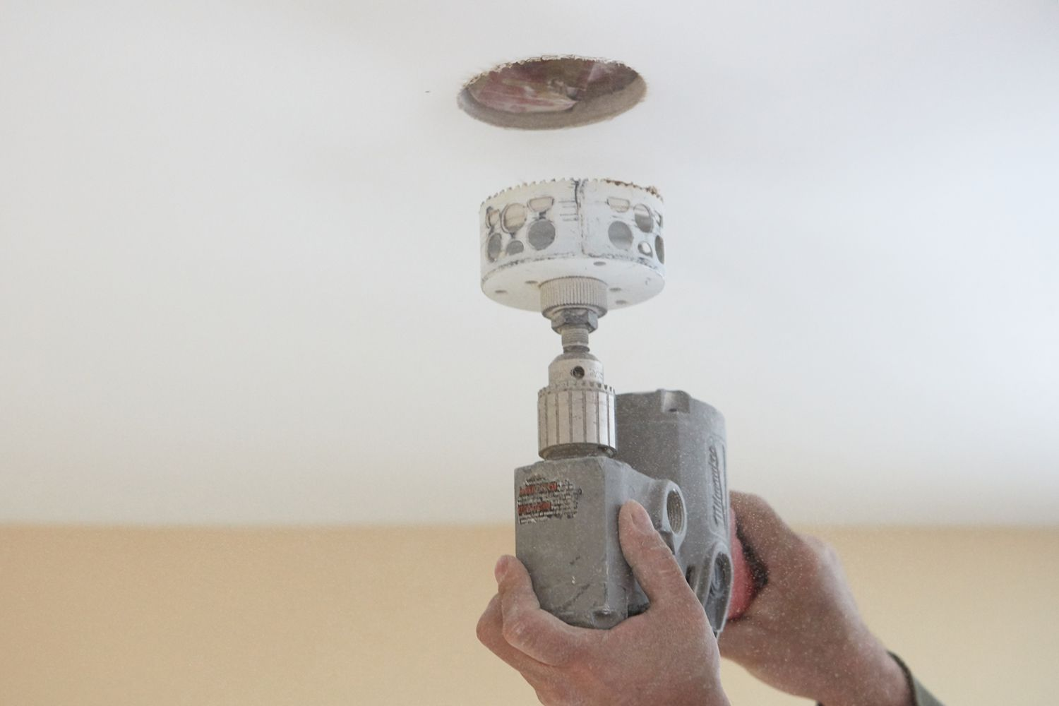 Hole being cut in ceiling for recessed lighting