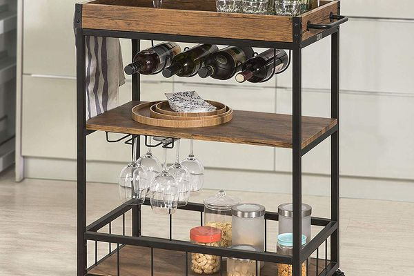 Rolling bar cart filled with wine, snacks, and glasses.