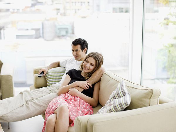 A couple sitting on sofa watching television