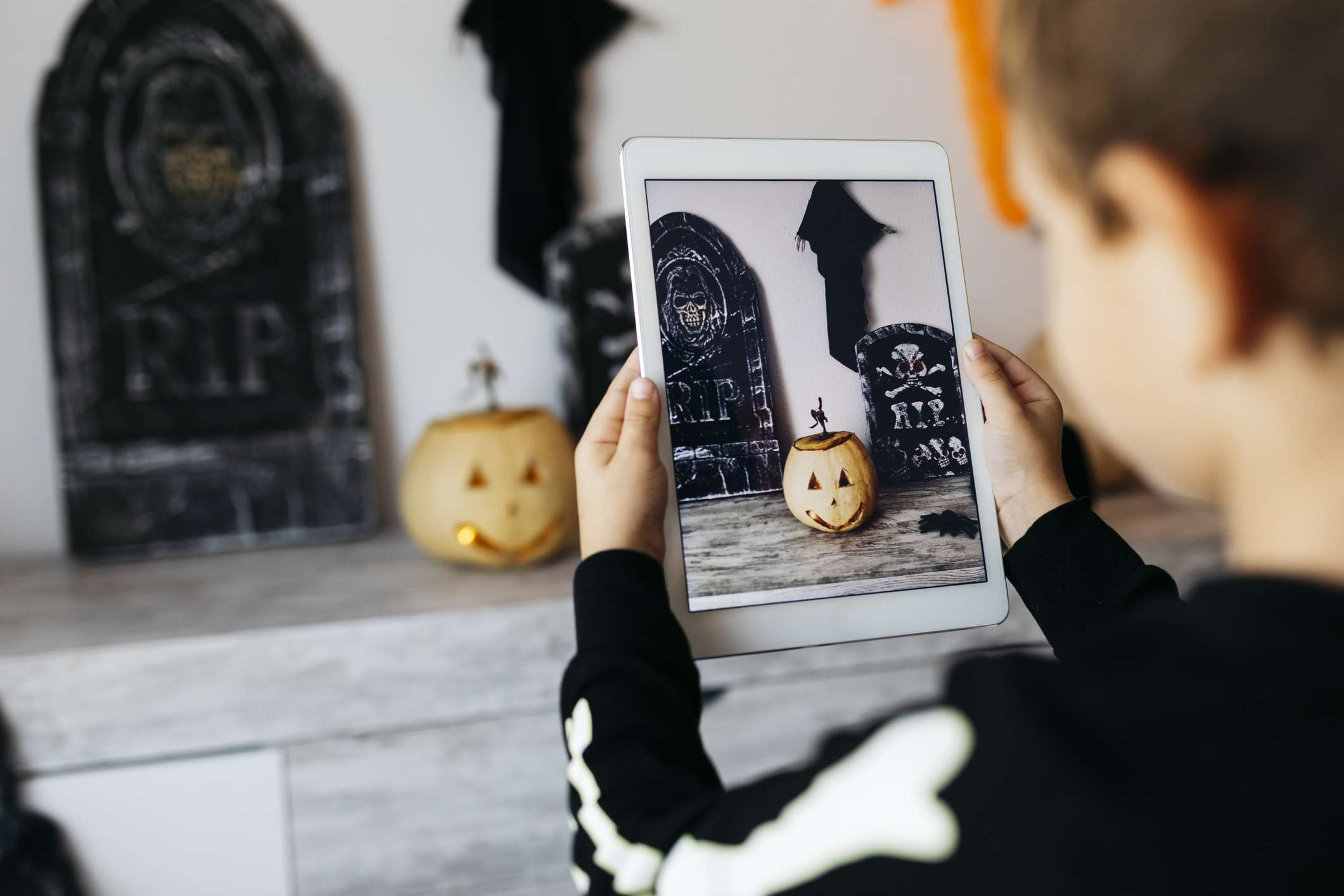 Little boy taking photo of Halloween decoration with digital tablet