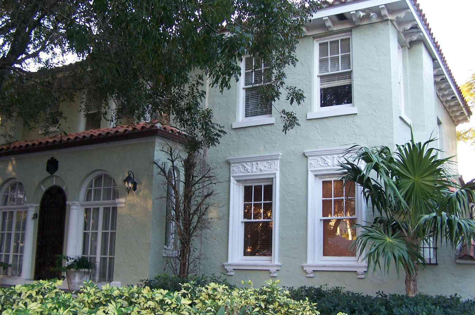 Estuco verde pálido, molduras blancas, dos pisos, aleros colgantes, entrada frontal con ventanas y puertas arqueadas