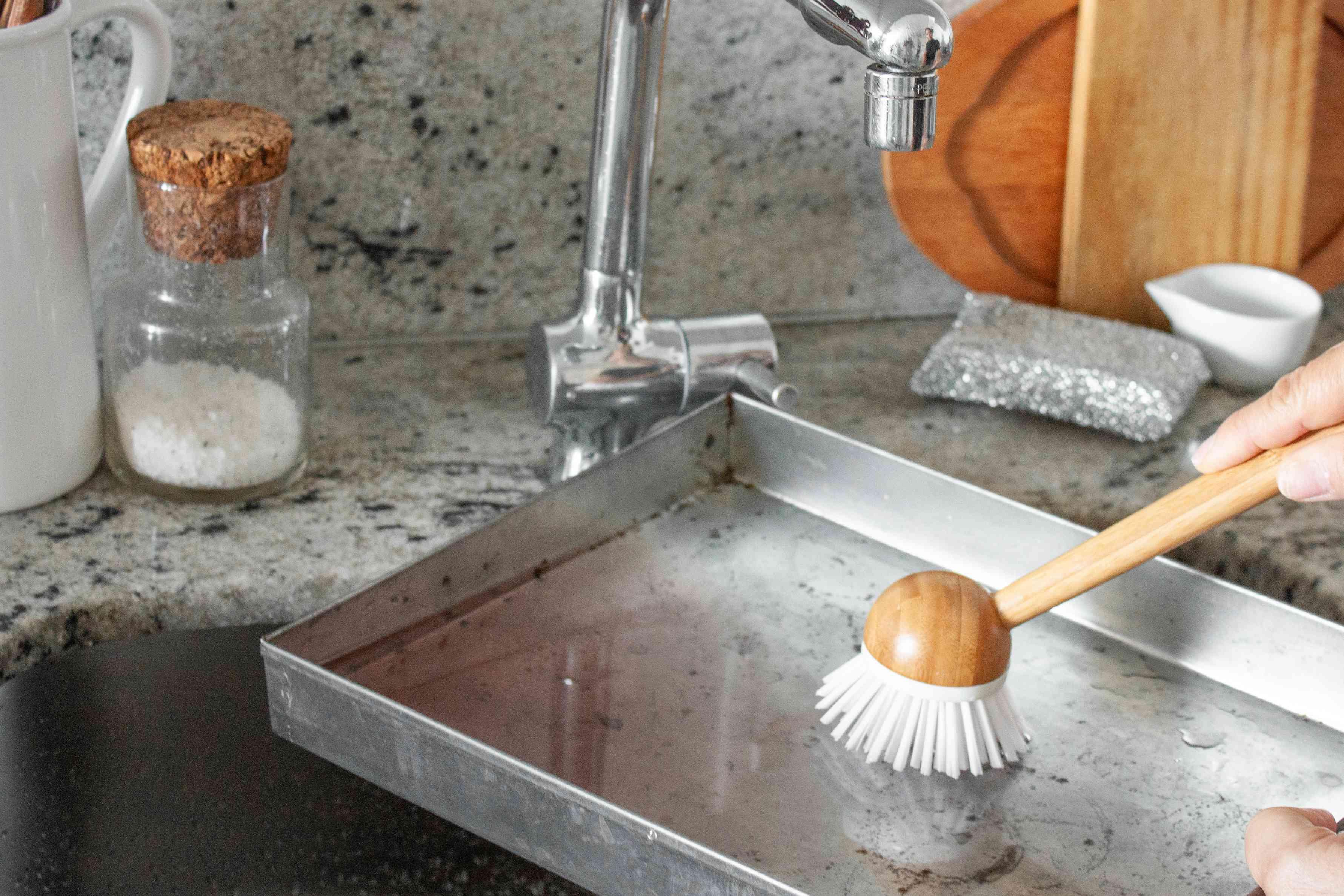 person scrubbing a pan