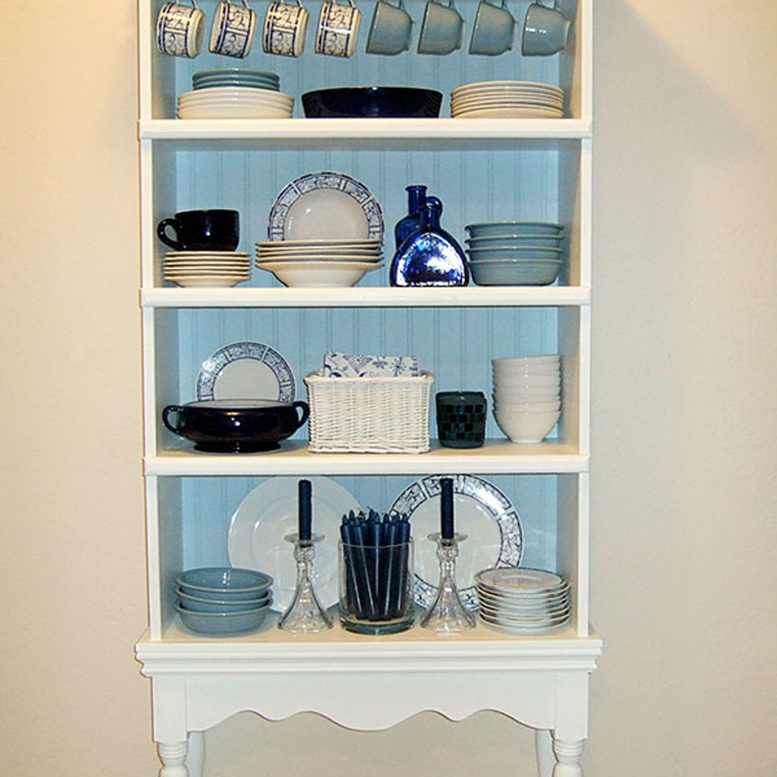 Bookcase repurposed as a china hutch with a blue background.