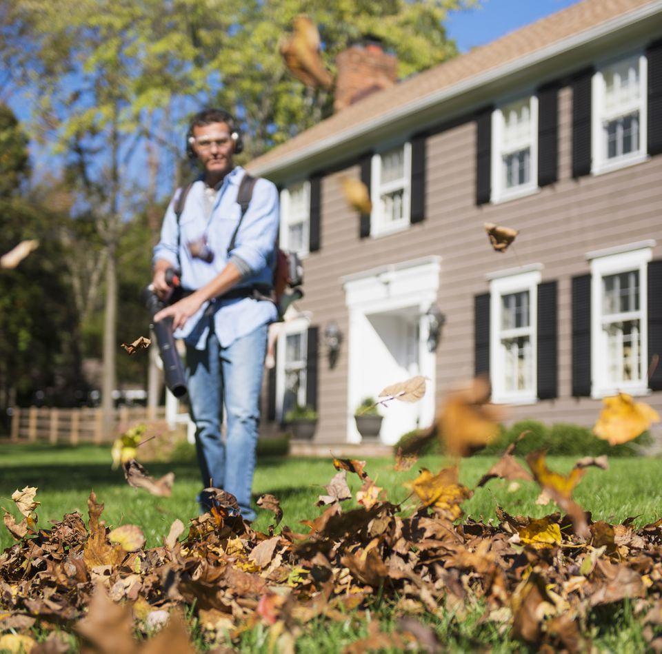 Man using leaf blower in front yard