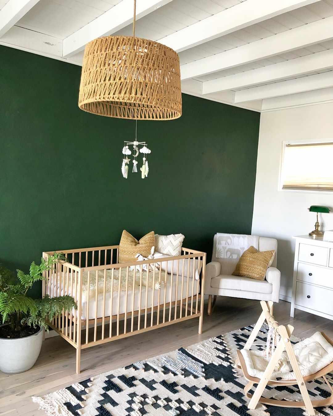 Boho nursery with dark green accent wall