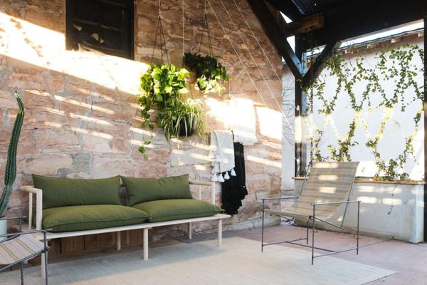 A porch with a green couch