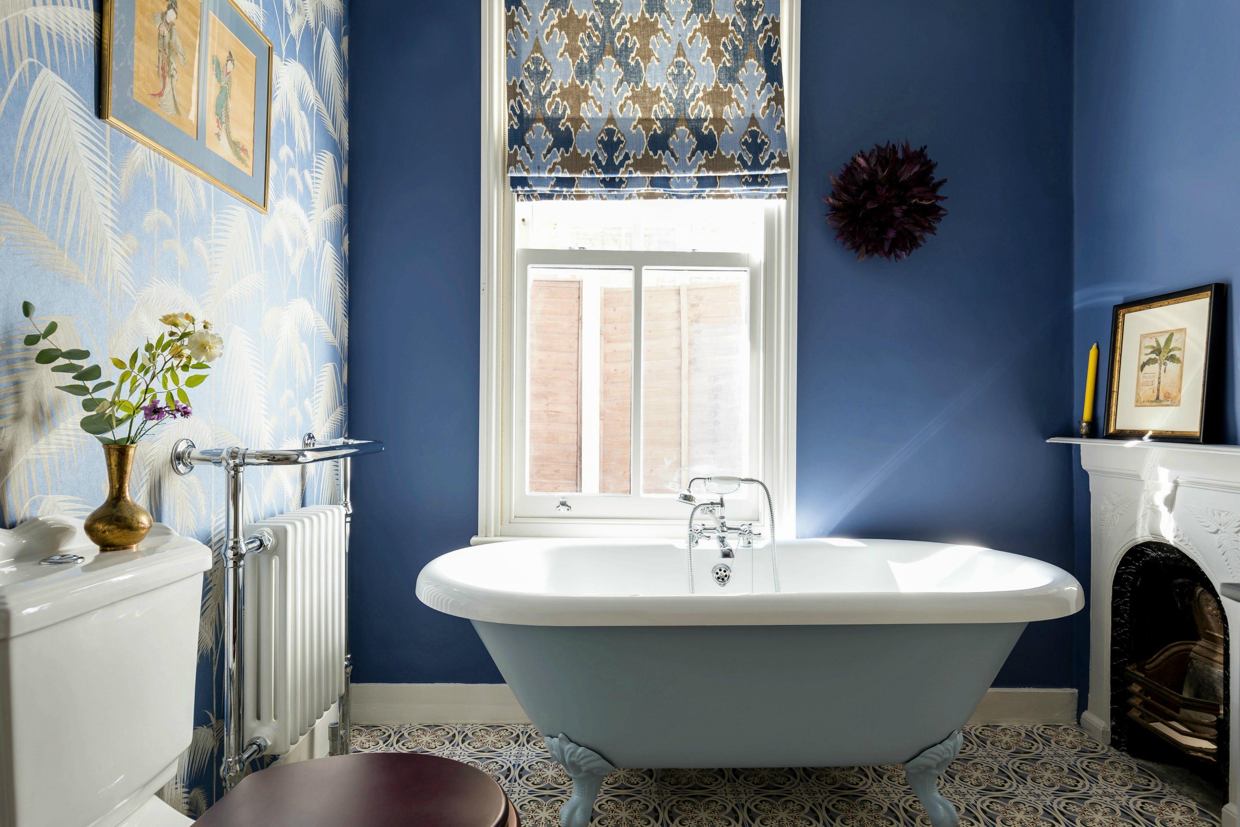 Un baño maximalista azul con bañera con patas