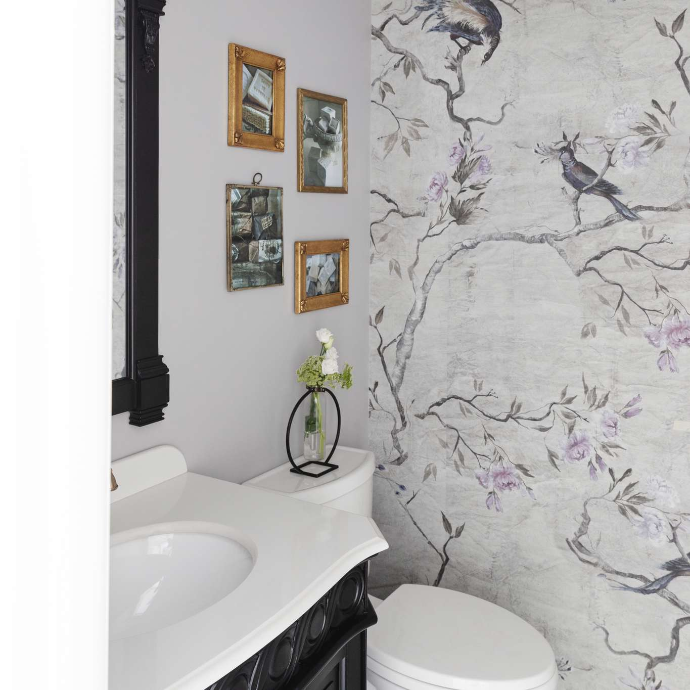 a purple and gray wallpaper mural with trees and birds used in a gorgeous powder room