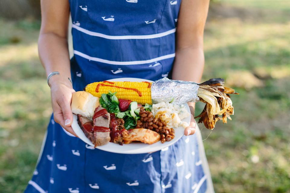 Woman holding plate of barbecue food, including beans, rolls, and meat.
