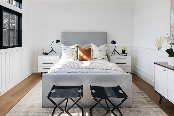 Bedroom made over with matching white nightstands and lamps and foldable chairs in front of gray bed