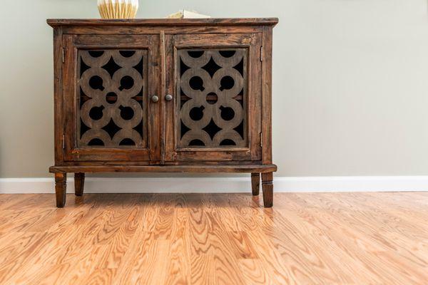Dar wooden cabinet with decor on light hardwood floor