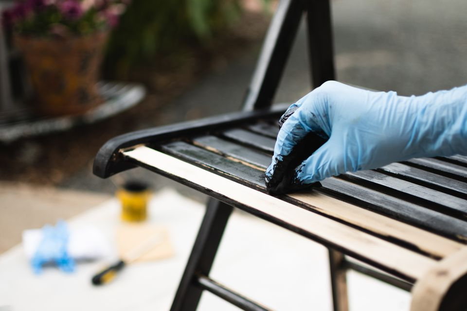 Wooden chair being covered with black wood stain while wearing blue gloves