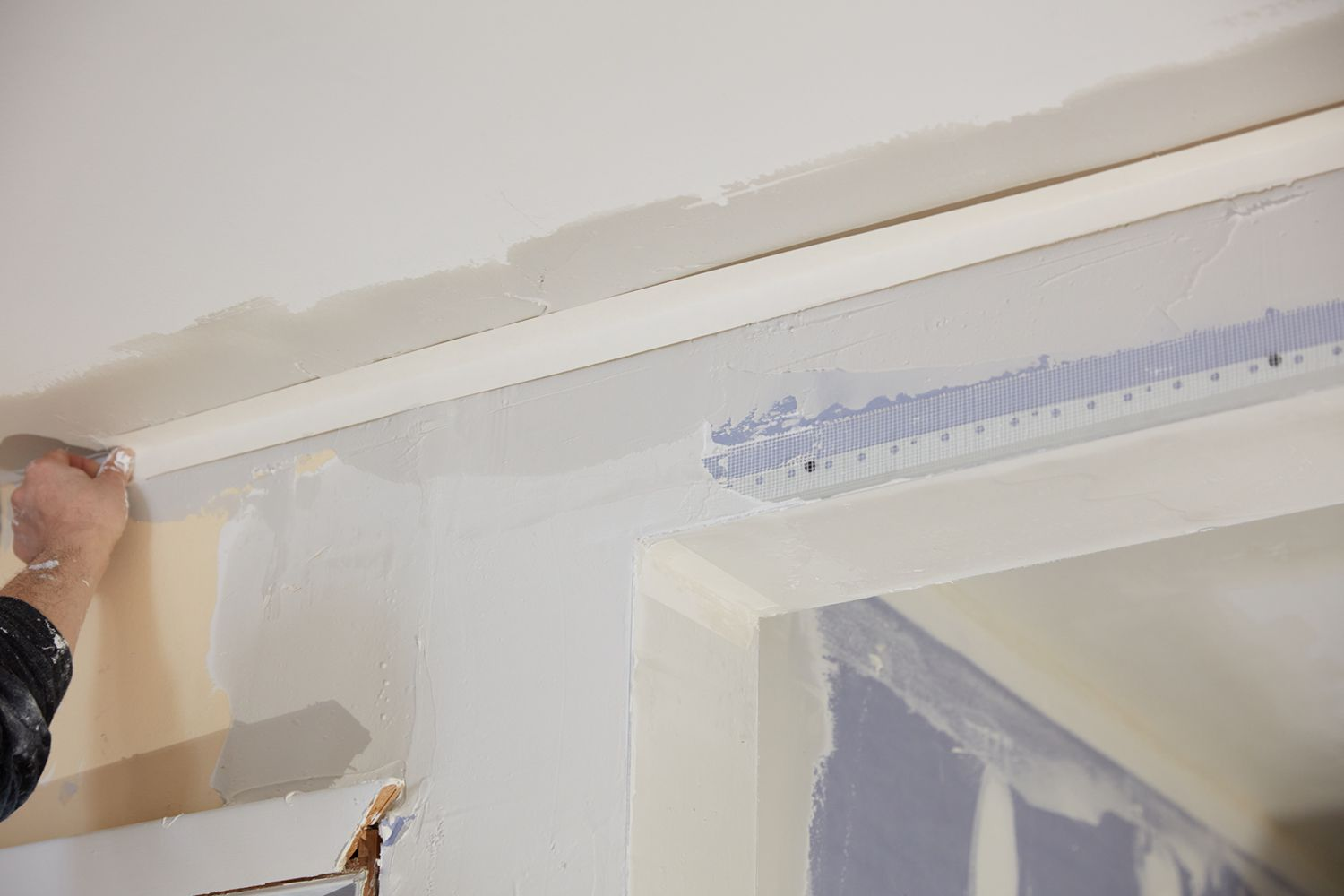 Patchwork and new trim added to top corner of load bearing wall