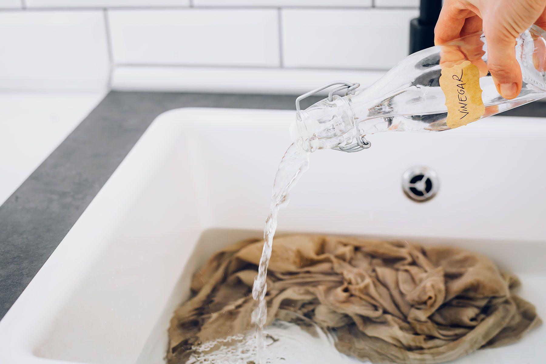 woman hand-washing a garment and adding vinegar