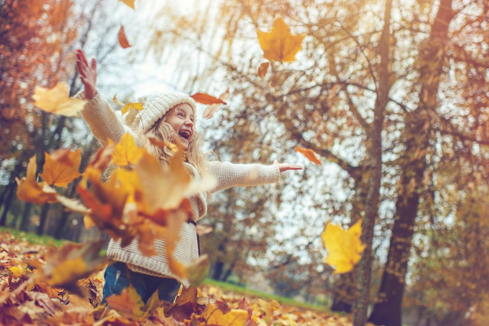 Young girl playing in fall foliage