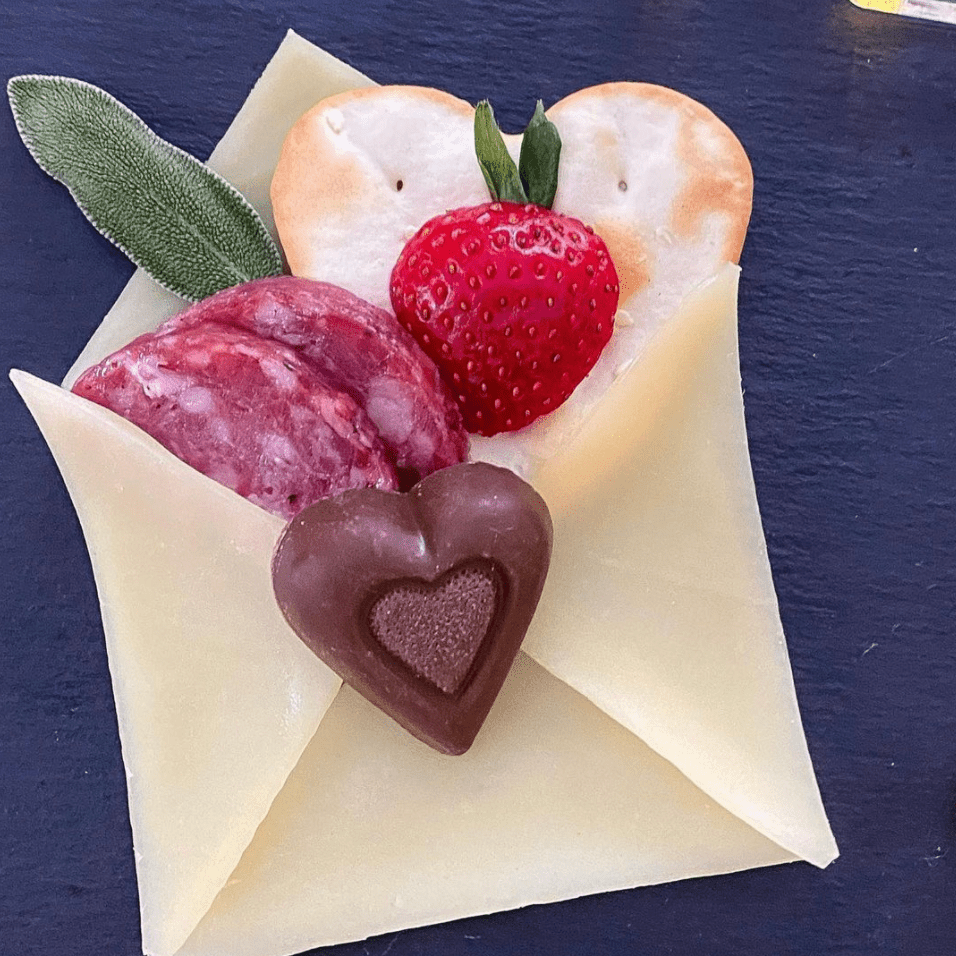 Charcuterie Valentine made of cheese, salami, cracker, sage, and chocolate