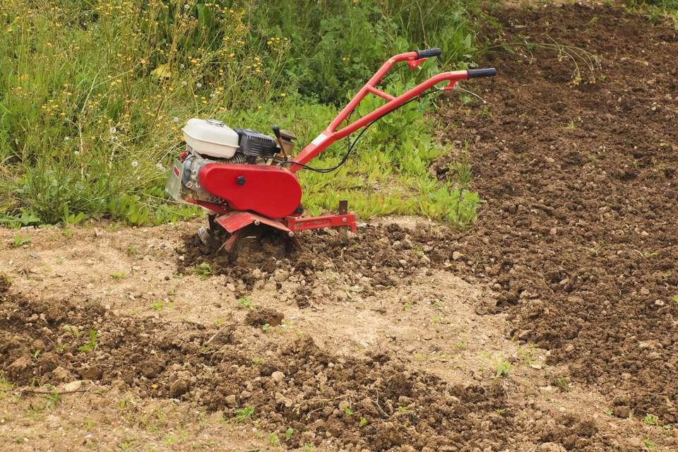 Small garden tiller cultivating soil.