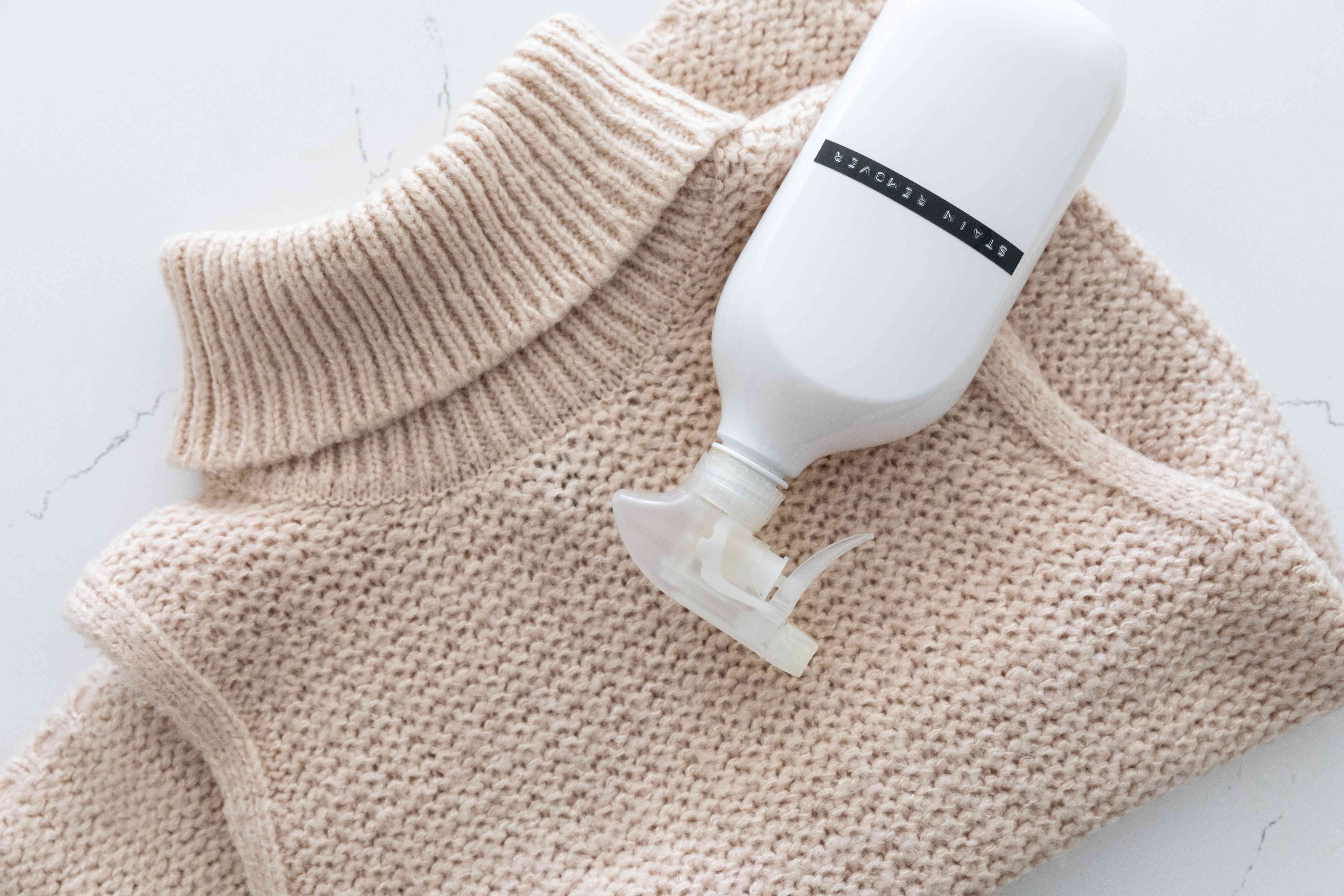 Acrylic knitted sweater spot treated with stain removal spray bottle on top