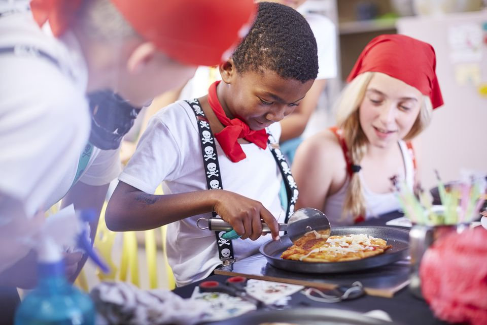 Kid eating pizza at pirate themed birthday party