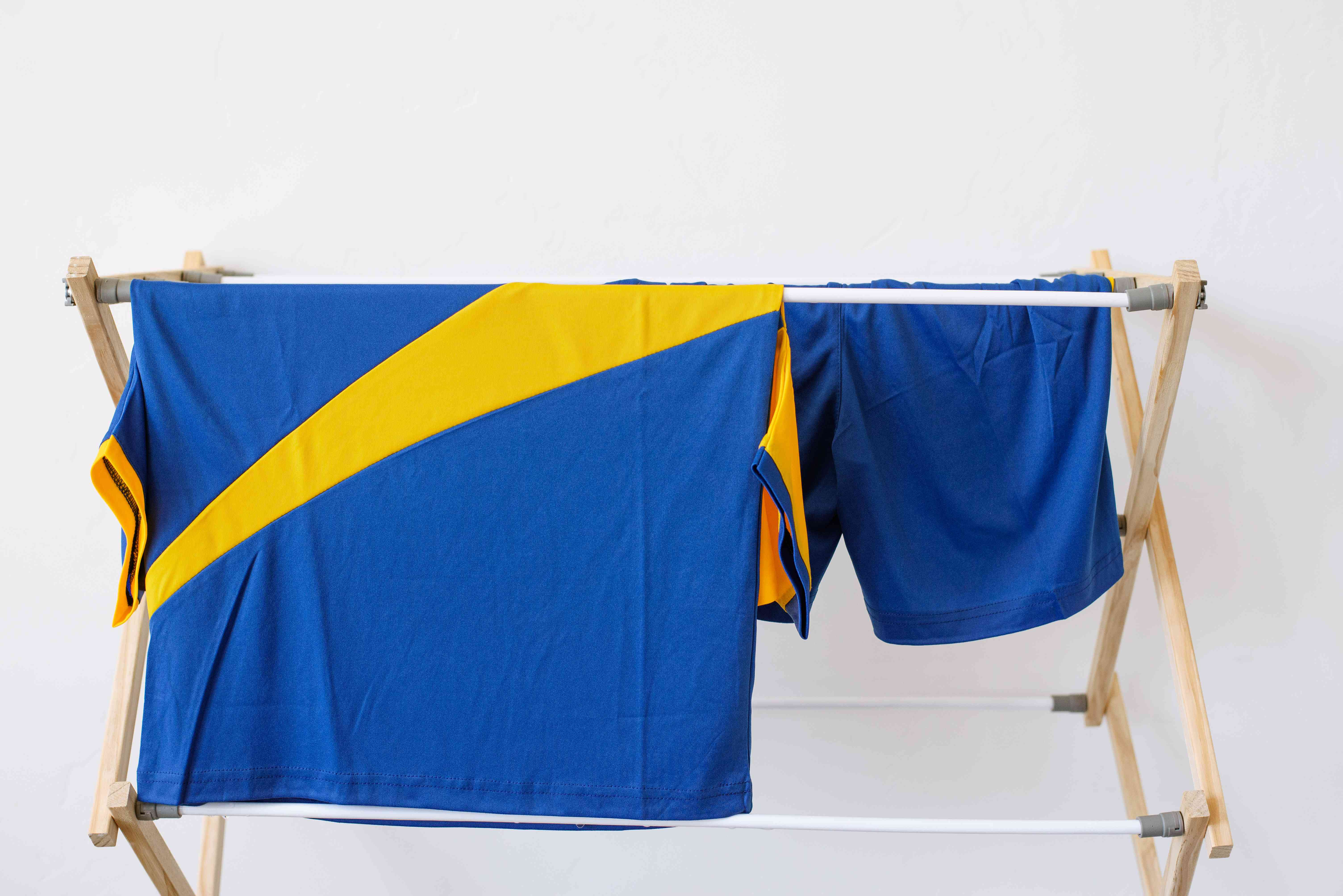 Blue and yellow soccer uniform hanging on drying rack to air dry
