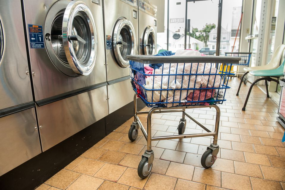 Industrial washing machines in public laundromat, with laundry in basket