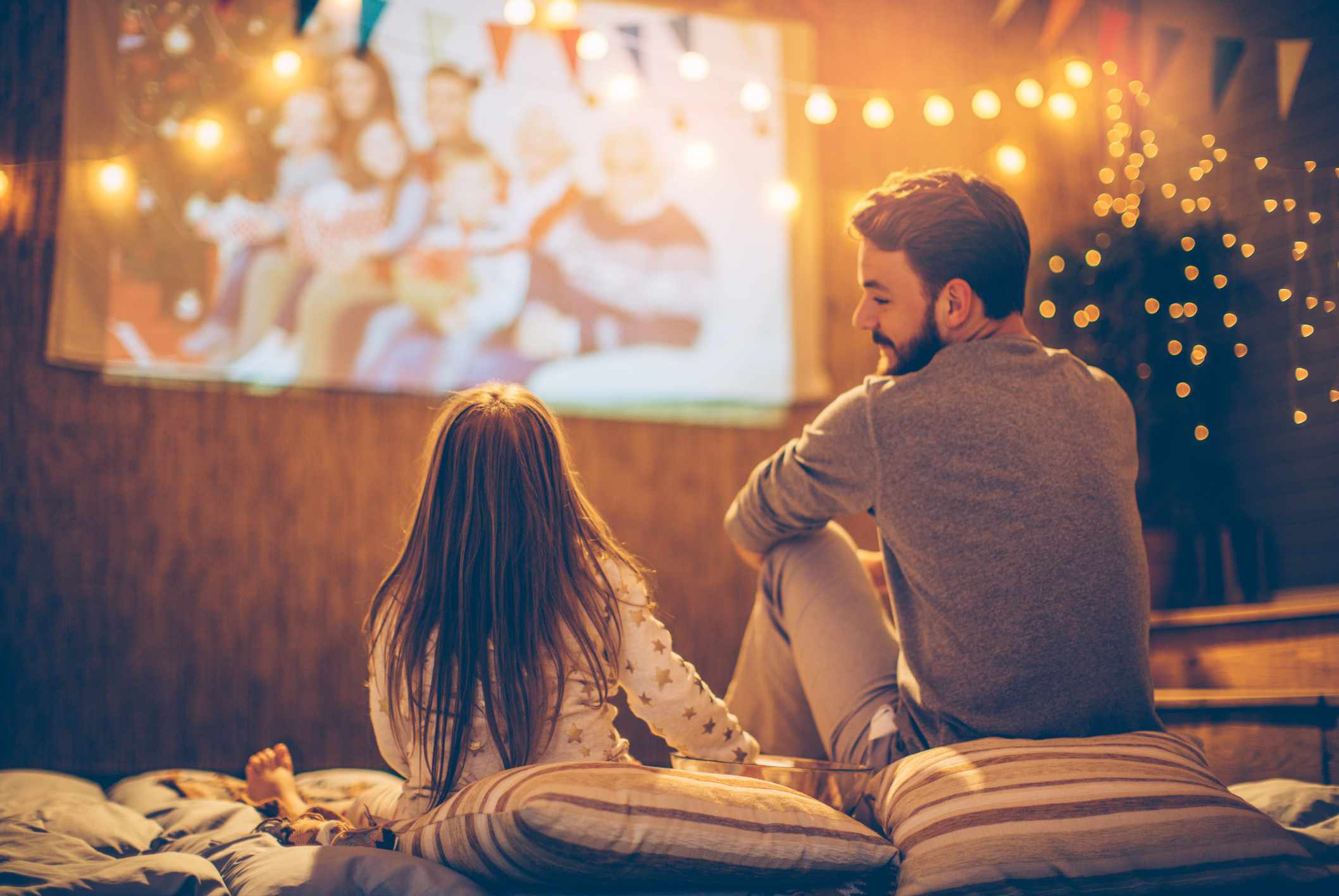 Father looking at daughter watching movie outdoors