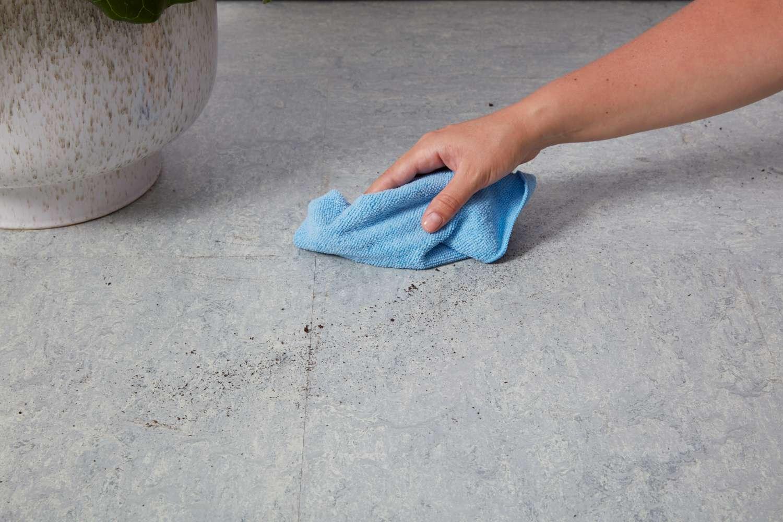 Wiping linoleum floor with microfiber cloth