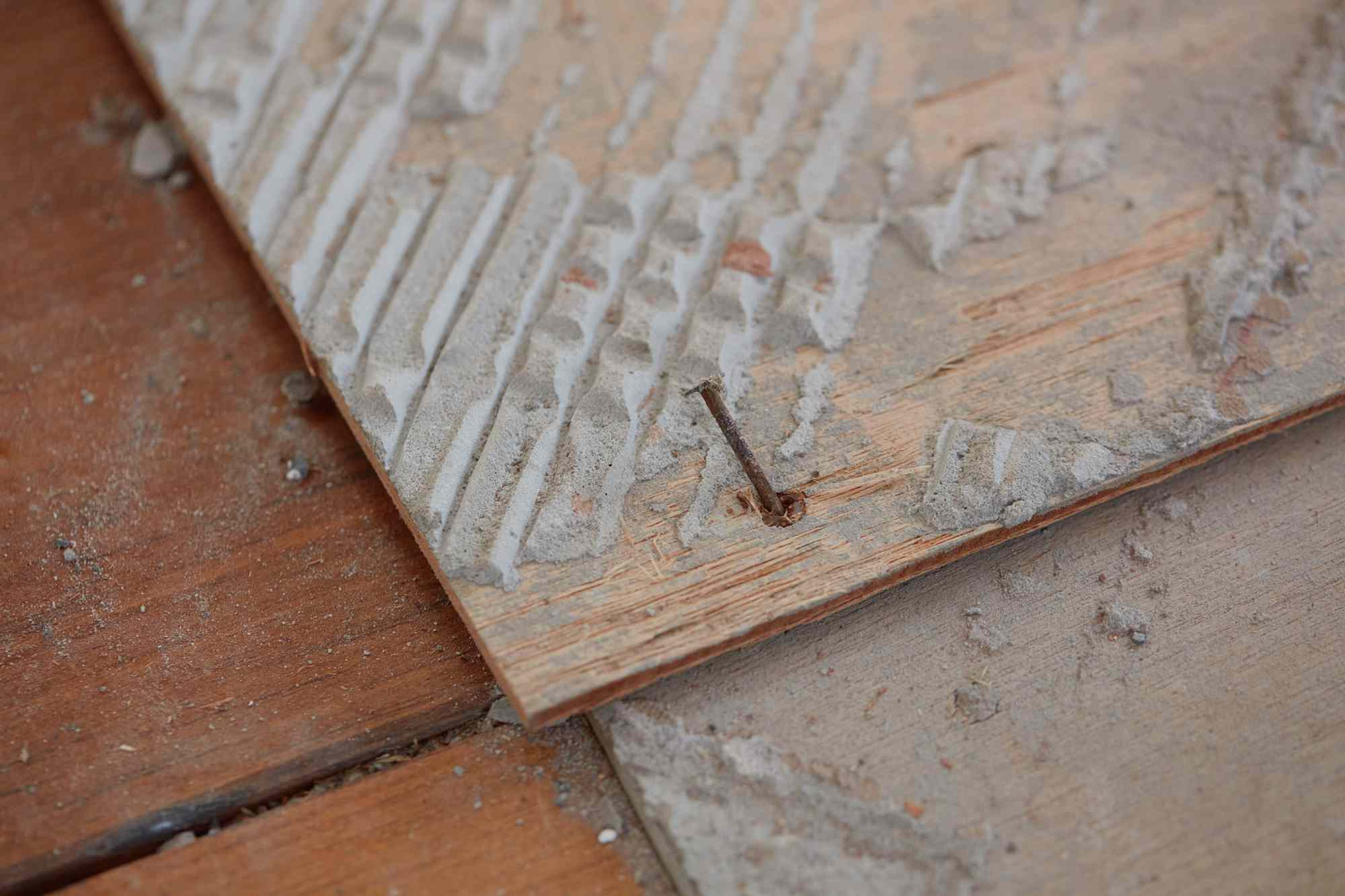 Plywood underlayment with nail for tile removal