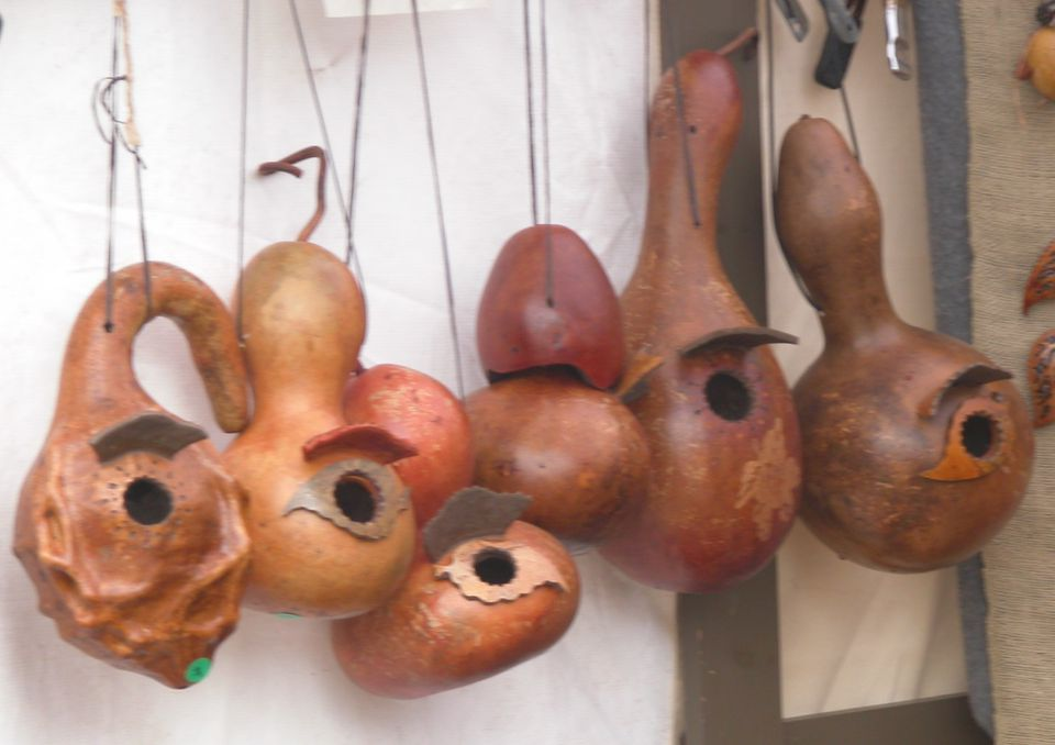 Six dried gourds made into birdhouses.