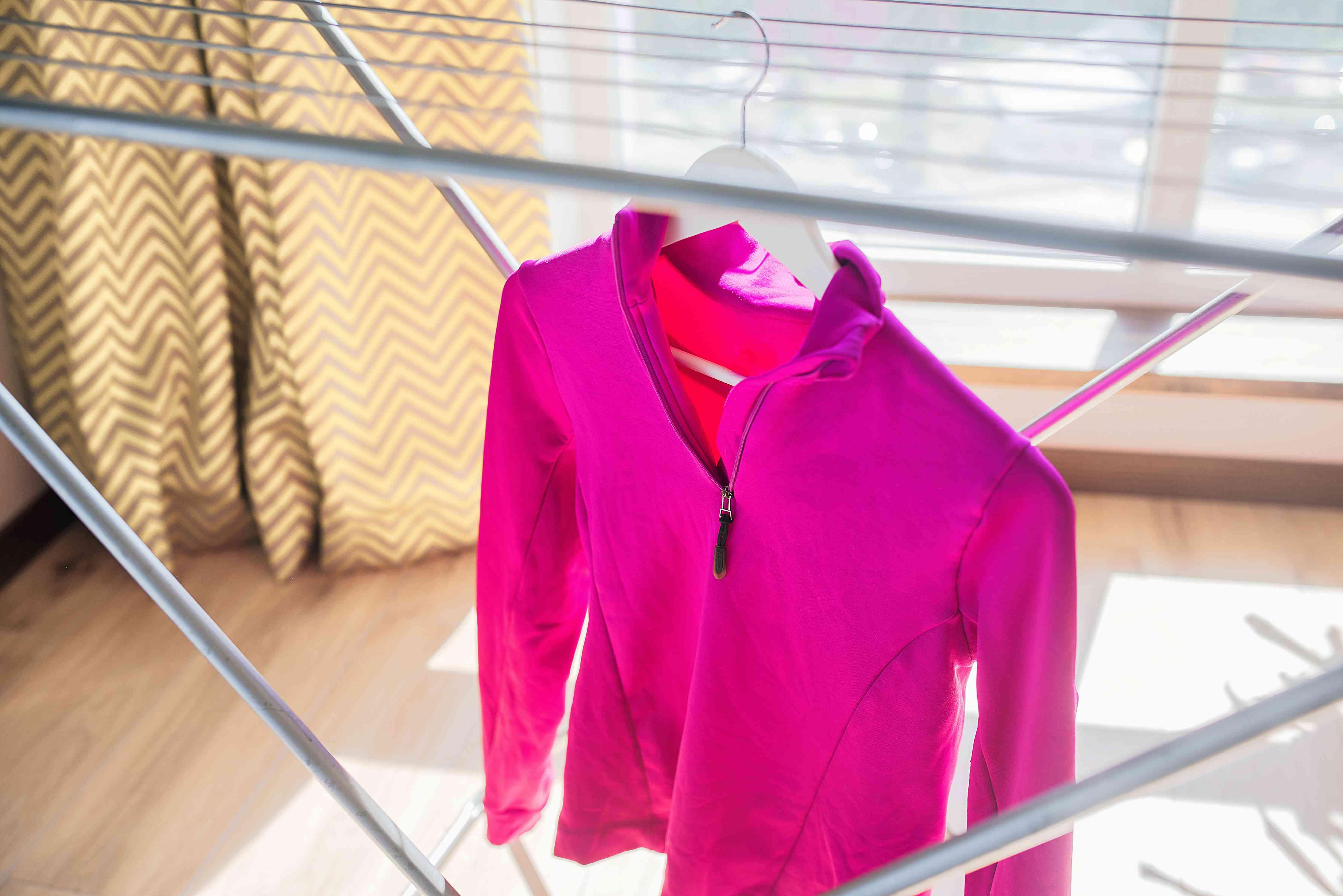 Pink fleece jacket on white hanger air drying on metal drying rack