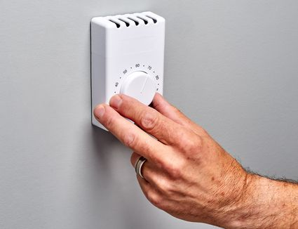 Line-voltage thermostat wired for a baseboard heater being adjusted