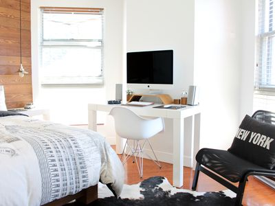 Bedroom with one wood paneled wall and desk with large monitor.