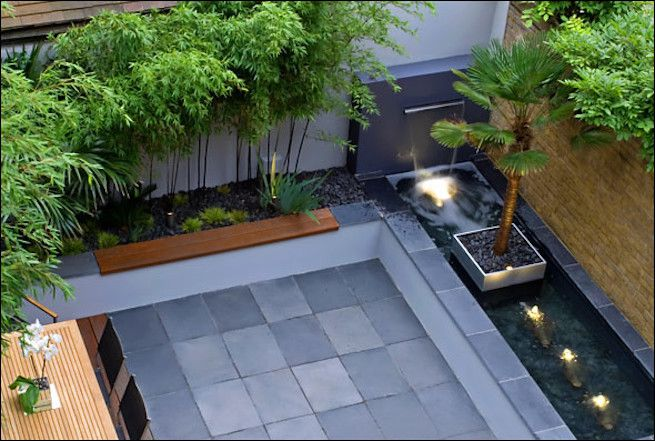 overhead shot of seating area with grey stone patio, small lights and potted trees