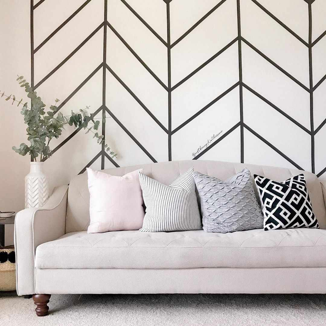 Couch with striped wall behind it