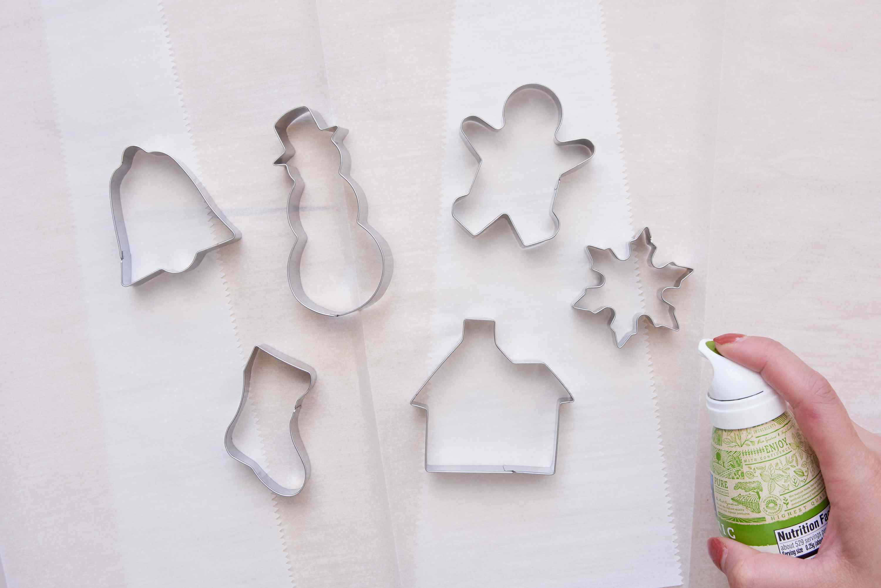 spraying the cookie cutters with cooking spray