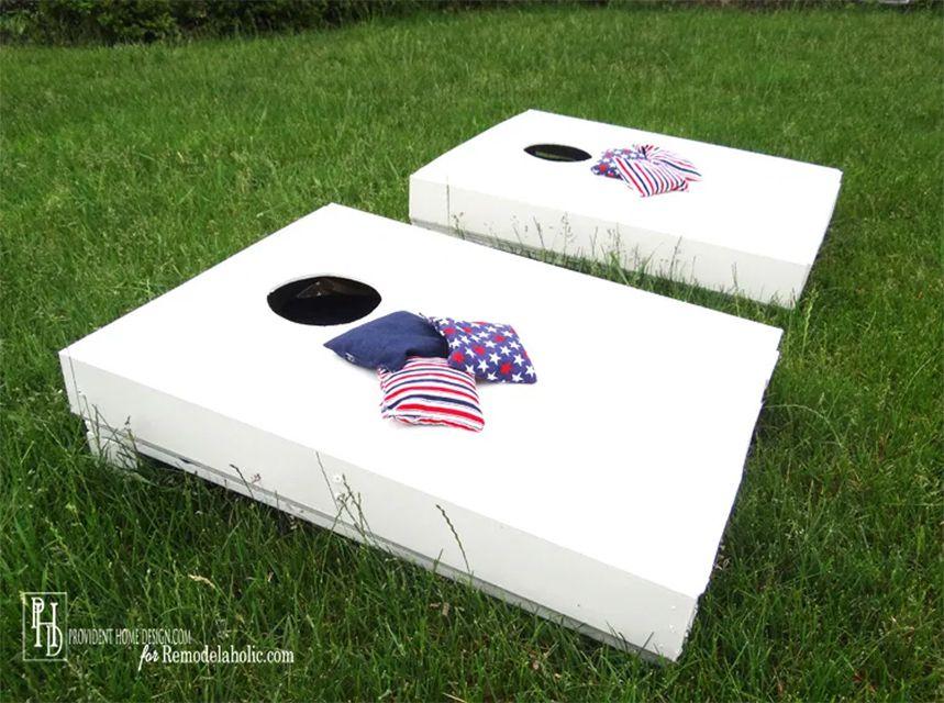 Two white cornhole boards in a yard