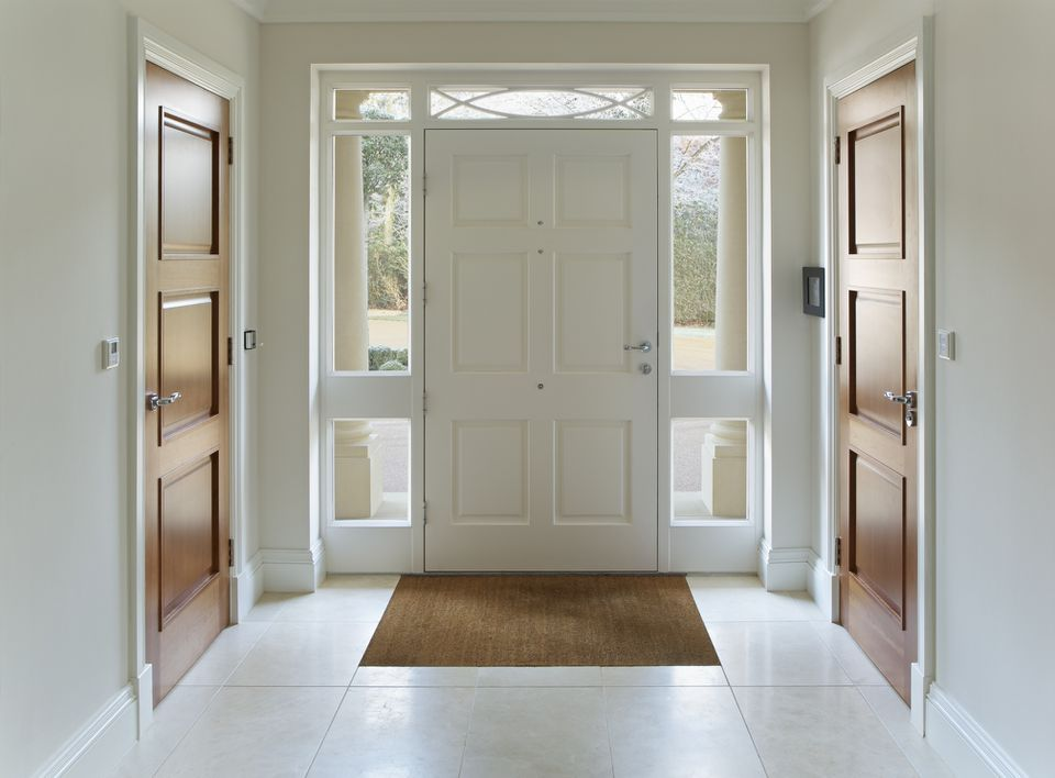 Front door entrance to an open hallway with two doors on opposite sides of the wall.