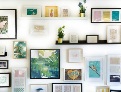 Various artworks and shelves hanging on white wall