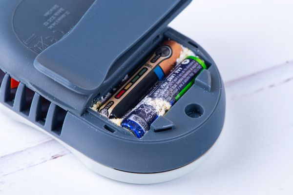 Battery acid exposed in the back of a blue electronic device