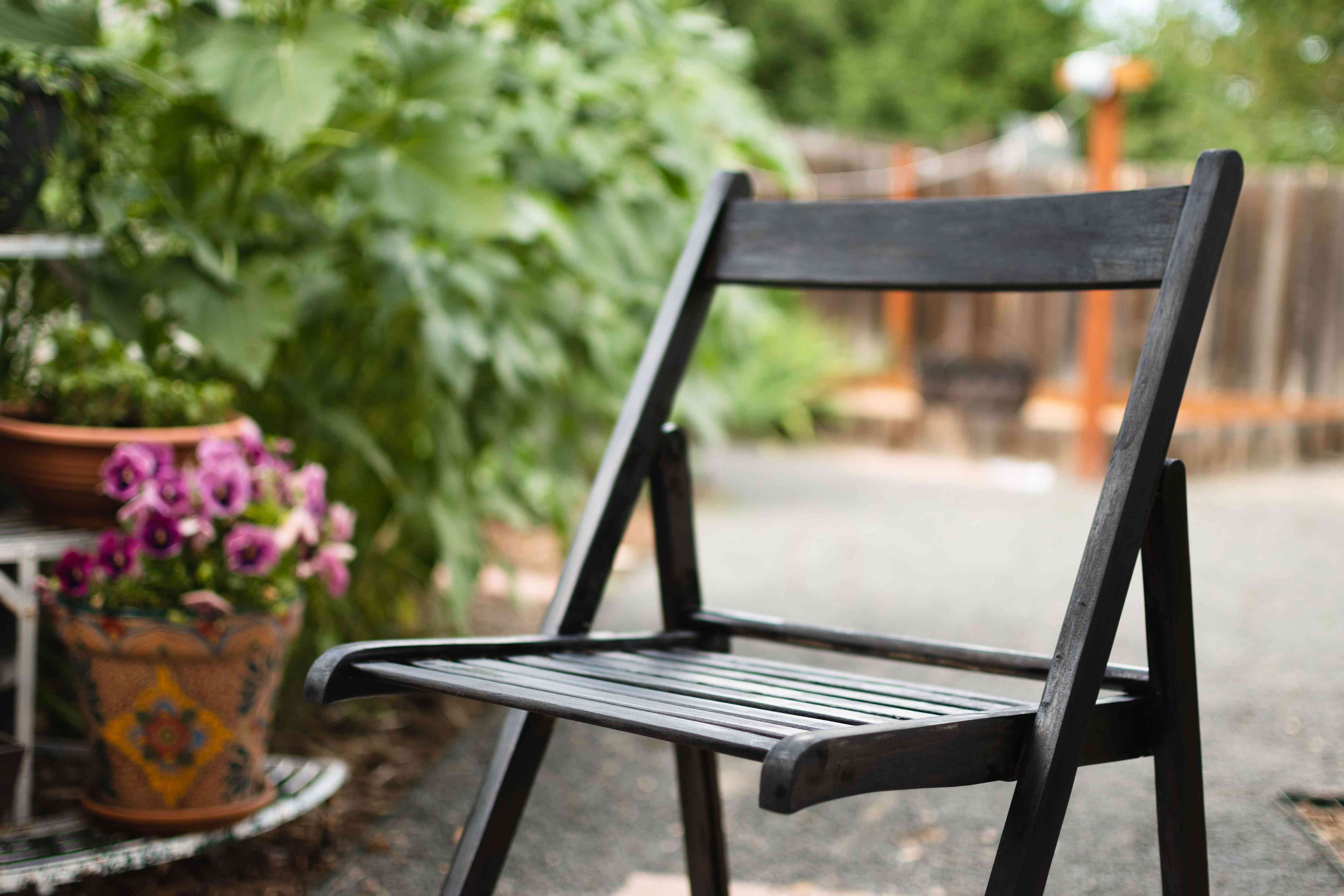 Wooden chair with fresh black stain sitting out to dry