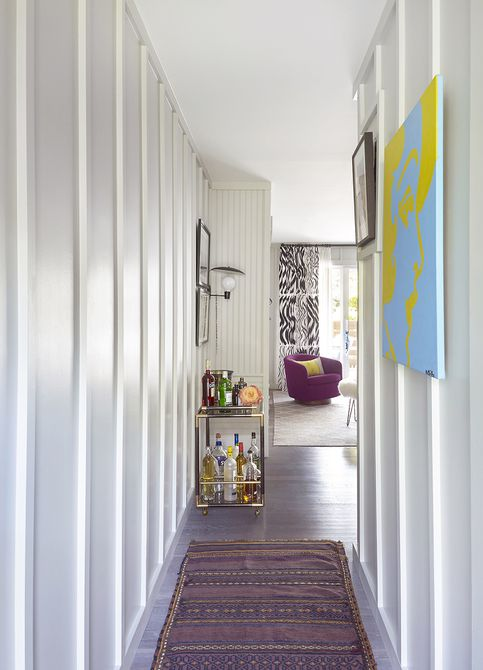 Hallway with colorful art and kilim runner