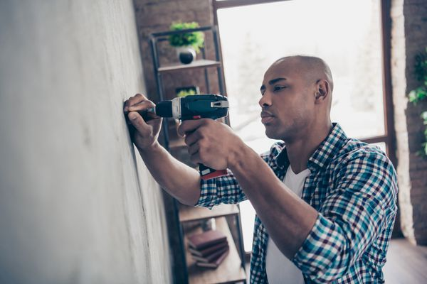 a home repairman drilling a hole in a wall
